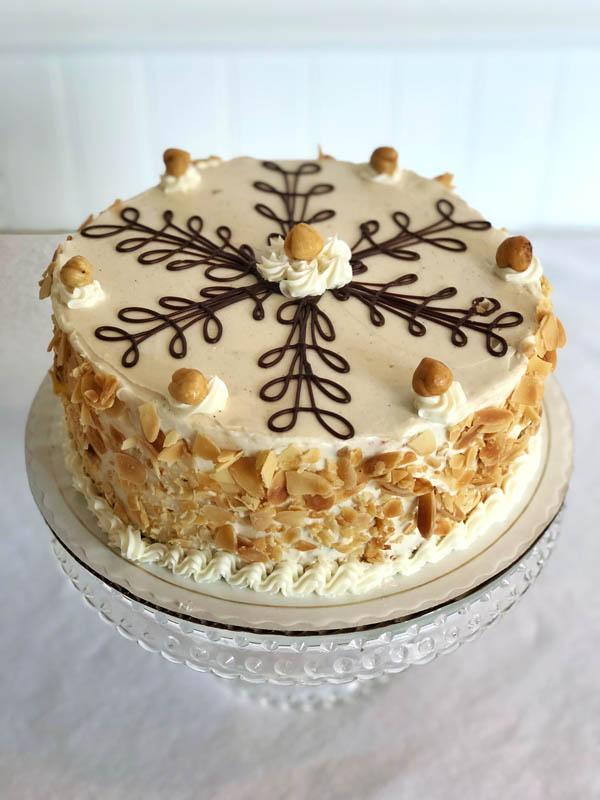 Hazelnut Dacquoise (gluten free) ~ Hazelnut meringue layers filled with dark chocolate mousse, praline whipped crème, and hazelnut buttercreme